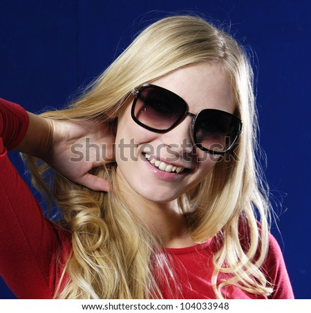 Sexy woman wearing sunglasses against blue background - stock photo