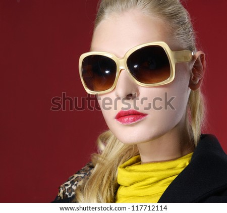 Sexy woman wearing sunglasses against red background - stock photo