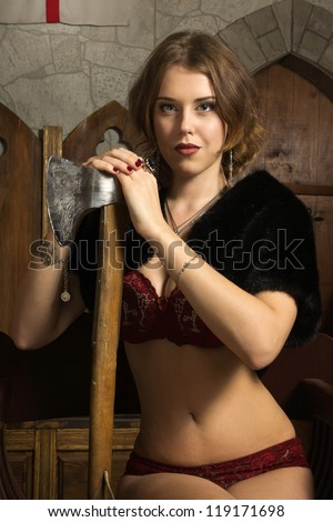 Sexy woman with axe in a medieval castle interior - stock photo