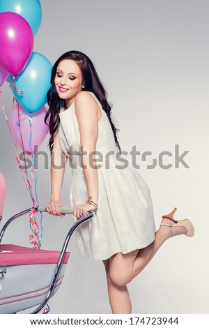 Sexy woman with baby stroller  - stock photo