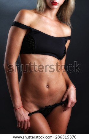 Sexy woman with black lingerie, posing against grunge wall. Close up.