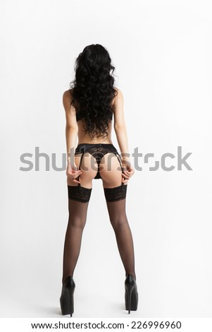 Sexy woman with black lingerie, suspenders and heels in the back - stock photo