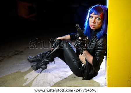 Sexy woman with blue hair holding two guns and looking as killer - stock photo