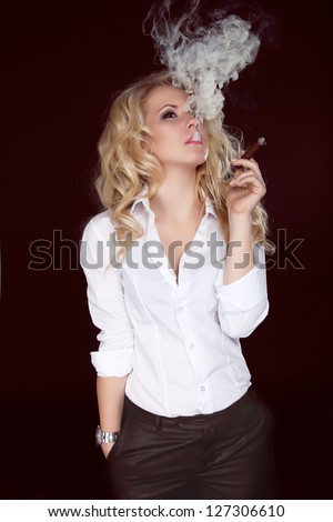 Sexy Woman with Cigar Exhaling Smoke on Dark Background - stock photo