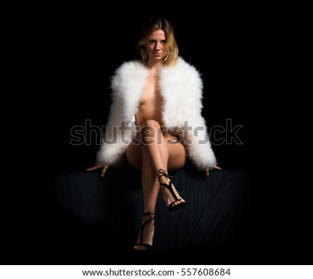 Sexy woman with feather coat on black background