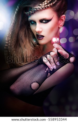 Sexy woman with haircut and art makeup is dancing disco 80 style. Party, dance, night, club.