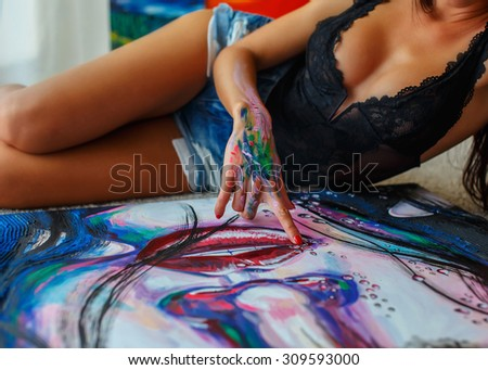 Sexy woman with long black hair in blue shorts laying on the floor with painting in front of her. - stock photo