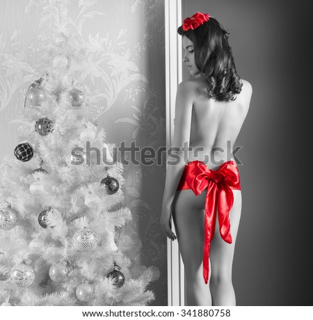 sexy woman with long hair, heels and nude body wearing only big red ribbon at waistline posing turned on her back . in black and white image