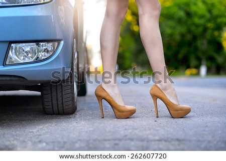 Sexy woman with long legs standing near the car on the road - stock photo