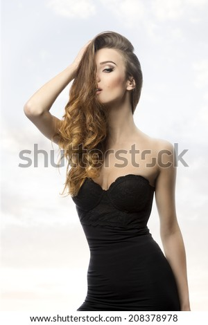 sexy woman with long wavy flowing hair on the face, sexy black dress and cute make-up, in sensual pose in fashion shoot  - stock photo