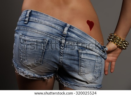 sexy woman with perfect ass showing her heart shaped tattoo on buttocks. Close-up of sexy bottom with denim shorts  - stock photo
