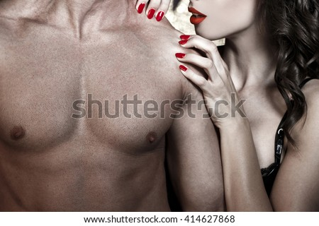 Sexy woman with red lips and nails playing on muscular mans shoulder, foreplay  - stock photo