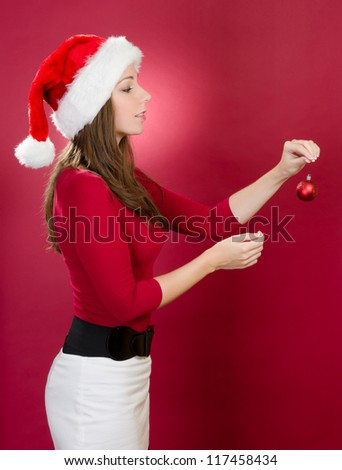Sexy woman with santa hat hanging a christmas ball - stock photo