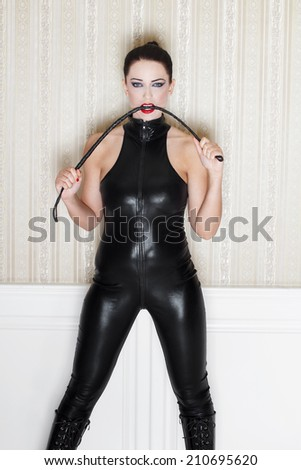 Sexy woman with whip in black latex catsuit, desire - stock photo