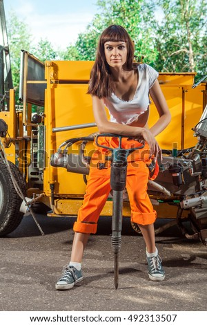 Sexy woman worker in overalls with the jackhammer.