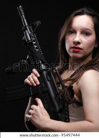Sexy women - Girl holding an Assault Rifle, black background - stock photo