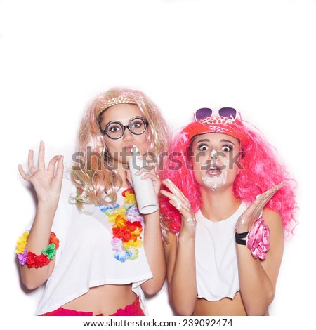 Sexy women in colored wigs and glasses stained with cream have fun .Two surprised girl friends opening mouth. White background not isolated - stock photo