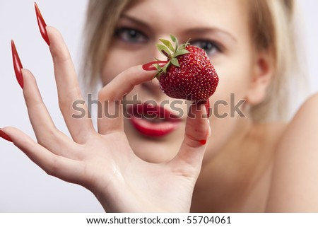 Sexy women with long red nails holding single strawberry