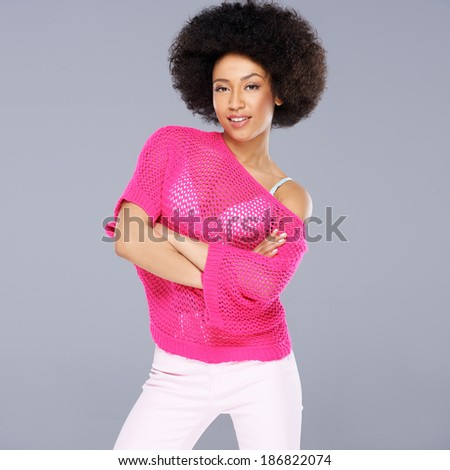 Sexy young African American woman with a frizzy afro hairstyle wearing a stylish pink blouse square format on grey - stock photo