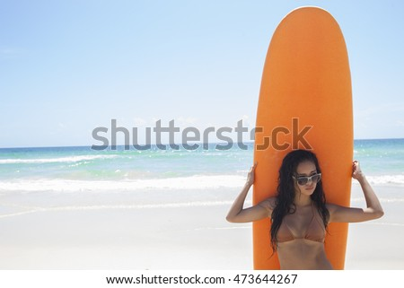 Sexy young asian woman wearing brown bikini and sunglasses with wet hair posing while holding orange surfboard during sunny summer day over blue sky, sea and sandy background