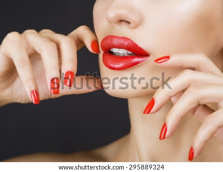 Sexy Young Beautiful Brunette Girl with Red Lips and Red Nail Polish, Bright Glistening Shining Make-up Closeup on Dark Background - stock photo