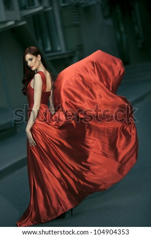 Sexy young beauty woman in fluttering red dress