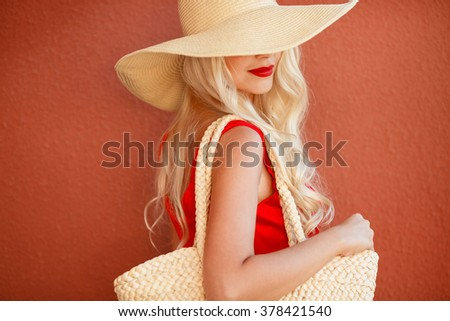 Sexy young beauty woman in red dress. beautiful fashionable blonde woman in red dress in hat with bag. Portrait Of Fashion Woman In red Dress Outdoor. fashionable woman standing by red wall  - stock photo
