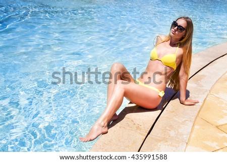 Sexy young blond fashionable woman posing in a yellow bikini - stock photo