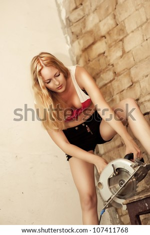 Sexy Young blond Woman builder Holding Circular Saw - stock photo