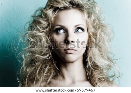 Sexy young blond woman posing on wall background - stock photo