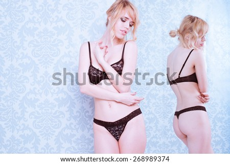 Sexy Young Blond Woman Wearing Black Lace Bra and Panties Standing Next to Mirror in Room with Patterned Wallpaper - stock photo