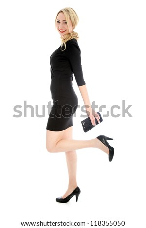 Sexy young blonde woman in black dress kicking back leg and holding a small black purse isolated on white background - stock photo