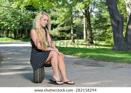 Sexy young blonde woman in black dress sits on a vintage suitcase outside near road -  in flip flops as well.  - stock photo