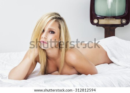 Sexy young blonde woman lying naked on bed - stock photo