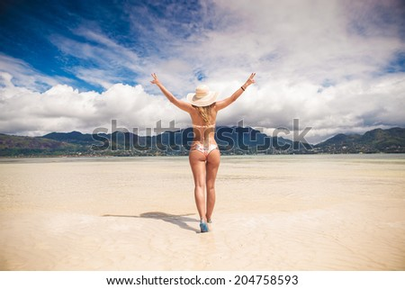 sexy young blonde woman walking with her hands in the air on a beautiful beach in seychelles