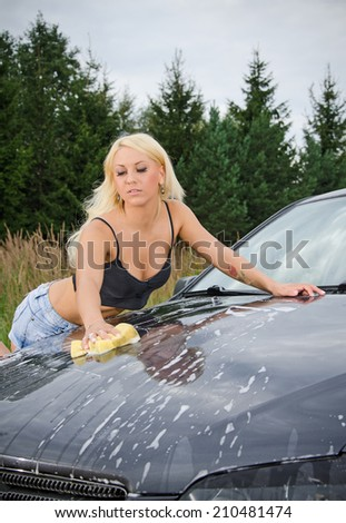 Sexy young blonde woman washes sport car. - stock photo