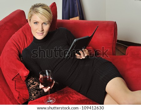 Sexy young blonde woman wearing a black dress holding a glass of red wine and reading an e-reader on a red couch - stock photo
