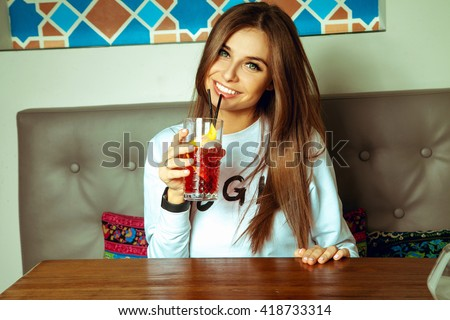 Sexy young brunette lady with green eyes drinks cocktail and smiling on camera - stock photo