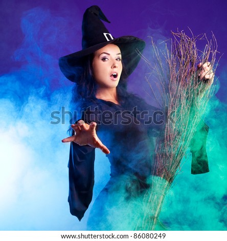 sexy young brunette witch with a broom stretching her hand to us, against purple background