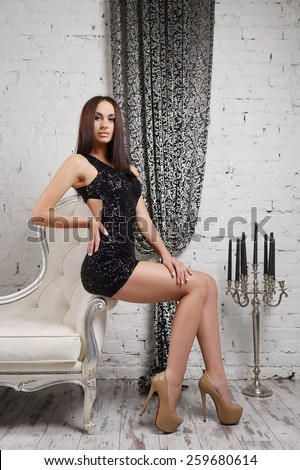 Sexy young brunette with large breasts and lush lips in black dress on a sofa in interior against the background of a brick wall with the curtain, on a wooden floor with a candlestick and candles  - stock photo