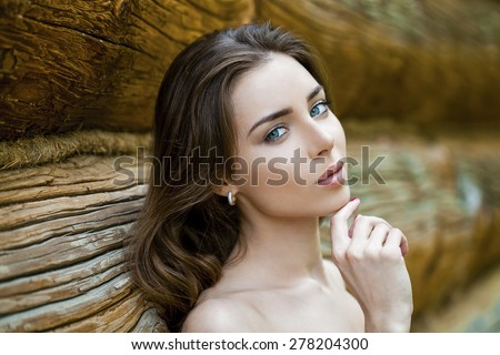 Sexy young brunette woman, against the background of the old wooden boards - stock photo