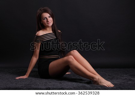 Sexy young brunette woman, wearing a black dress - stock photo