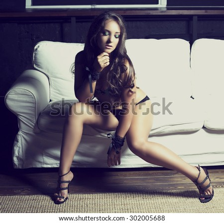 sexy young brunette woman wearing underwear on the sofa - stock photo