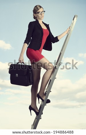 sexy young business woman walking on staircase with short suit and work bag  - stock photo