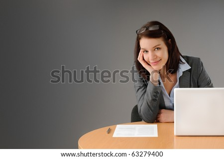Sexy young businesswoman sitting at her desk smiling - stock photo