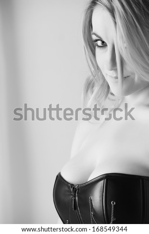 Sexy young Caucasian adult woman with soft curled blonde hair and a fuller figure in a light bedroom against a white wall, wearing a black leather corset. B&W Image - stock photo