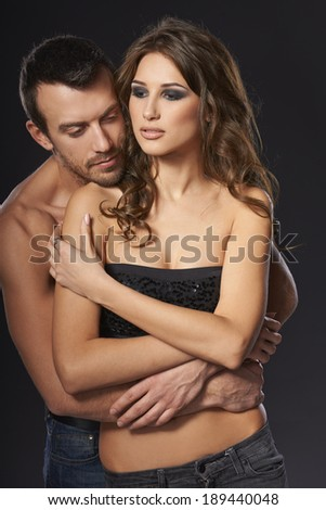 Sexy young couple embracing against black background