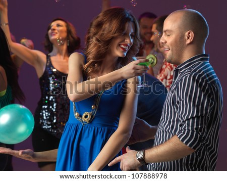 sexy, young couple having drinks on the dancefloor, in a night club - stock photo