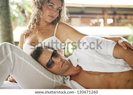 Sexy young couple hugging while lounging together on a tropical garden bed while on vacations in an exotic destination.