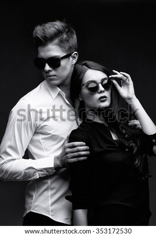 Sexy young couple in love. Studio shot on dark background